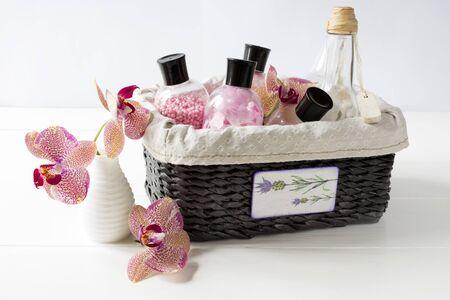 productos de belleza: Conjunto de cosméticos para el cuidado del cuerpo en una cesta de mimbre oscuro decorado con orquídeas en la mesa de madera blanca