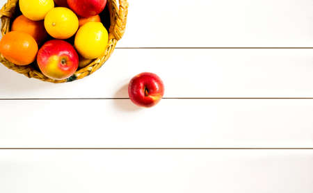 fruits in a basket: ripe fruits in a wicker basket on the white wooden table top view