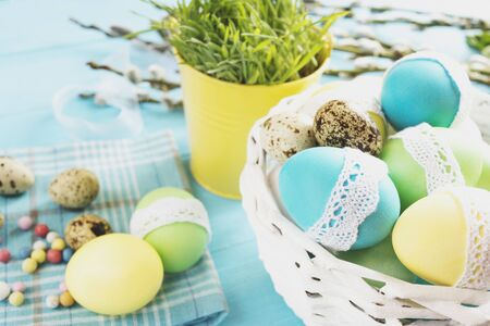 white eggs: colorful easter eggs in a white wicker basket on blue table against the backdrop of greenery in decorative yellow bucket