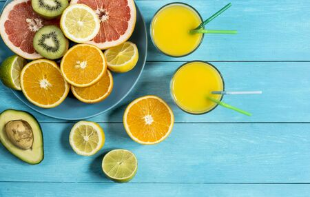 gean: ripe juicy citrus fruit juice ice on a blue wooden table top view