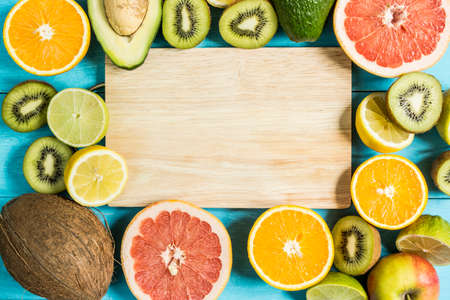 gean: citrus fruits in the center of a wooden board on a blue table top view