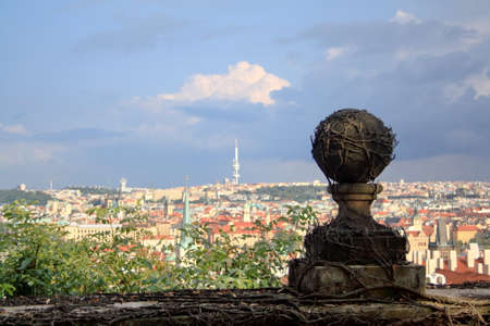 View of Czech Republic capital Prague with blue sky and clouds and stone ball with prickly vine