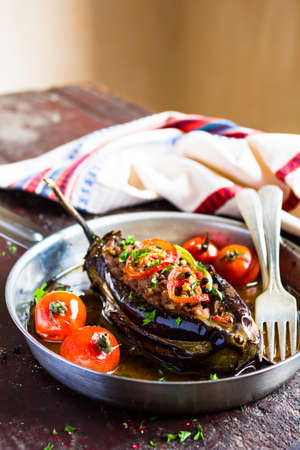 Traditional turkish dish called Karni Yarik, eggplant or aubergine stuffed with minced pork, beef meat, cherry tomatoes, chili pepper, parsley in a pan on a wooden table, selective focus Stock Photo