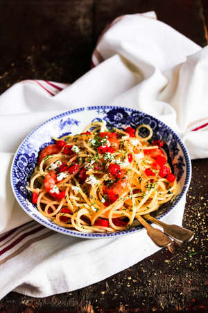 comfort food: Homemade spaghetti pasta dish with fried prawns, red bell pepper, feta cheese in a bowl on a wooden table, selective focus Stock Photo
