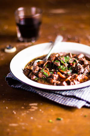 Homemade traditional irish beef stew or ragout with carrot, onion, parsley in Guinness beer, selective focus