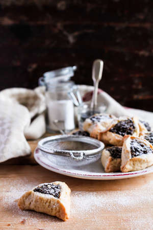 Homemade cookies or biscuits in shape with dates, poppy seeds, dusted with icing sugar, called Hamantaschen or Haman Ears special for jewish celebration of Purim, selective focus