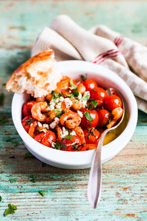 Homemade mediterranean meal with roasted cherry tomatoes, prawns or shrimps, fresh salted feta cheese, parsley served with freshly baked bread in a bowl on a wooden table, selective focus