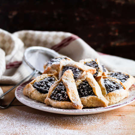Homemade cookies or biscuits in triangle shape with dates, poppy seeds, dusted with icing sugar, called Hamantaschen or Haman Ears special for jewish celebration of Purim, selective focus