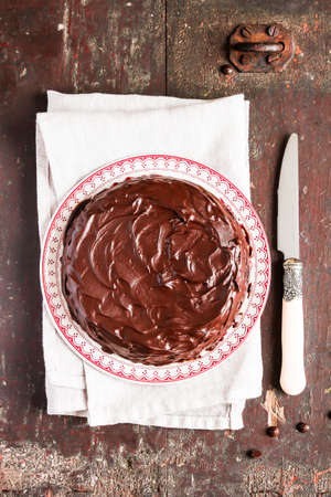 Chocolate cake with dark chocolate frosting on a plate with knife and napkin on a wooden table, selective focus