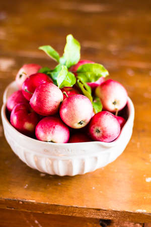 Fresh raw organic red apples in a bowl on a wooden table, selective focus. Harvesting time. Healthy and organic food option. Stock Photo