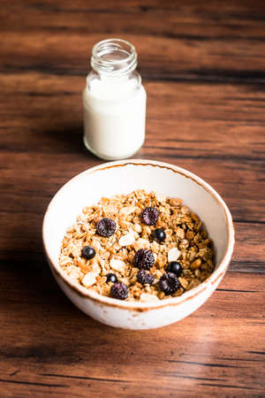 Breakfast super bowl of homemade granola or muesli with oat flakes, black currant, black raspberry and peanuts on a wooden table, selective focus. Served with a bottle of fresh milk. Organic food.
