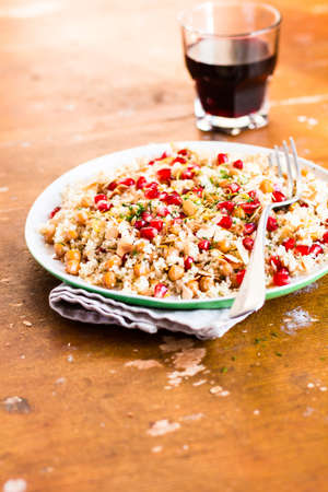 Traditional east asian meal. Plate of warm salad with couscous, chickpea, pomegranate seeds, lemon zest, almond flakes and dill on a wooden table, selective focus. Healthy and organic food option.
