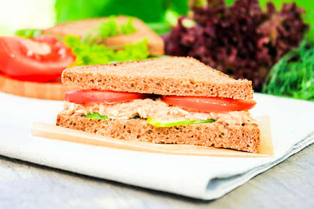 Sandwich with rye brown bread, ripe tomatoes, cucumbers and tuna fish for healthy snack on a napkin on a wooden table, selective focus Stock Photo