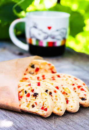 Heap of delicious Italian cantuccini cookies with dried cranberry, raisin, pistachios on a wooden table, selective focus. Summer picnic food. Biscotti cookies. Traditional italian food.