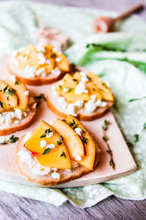 Fruit summer snack. Traditional italian food. White bread with peach fruit, salted feta cheese, honey and thyme served on a wooden cutting board, selective focus. Bruschetta for a picnic.