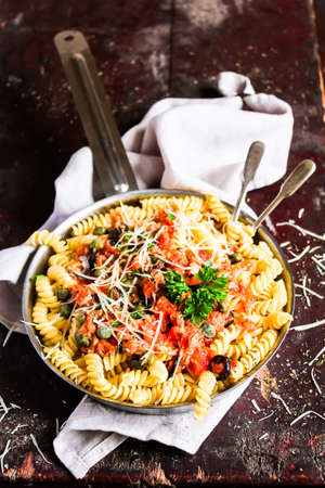 Pasta fusilli meal with canned tuna fish, tomato sauce, black olives, grated cheese and parsley in a cooking pan pn a wooden table, selective focus. Traditional Italian food. Comfort food.