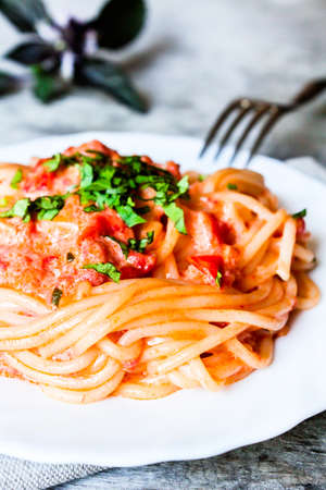 Traditional italian food. Pasta spaghetti alla vodka with cream sauce, tomatoes, parsley and basil on a plate on a wooden table, selective focus. Comfort food. Vegetarian style pasta. Stock Photo
