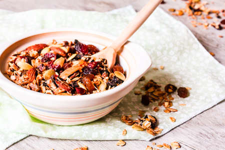 Granola breakfast with raisin, dried cranberry, almond nuts, pumpkin seeds in a bowl, selective focus. Organic and healthy food concept.