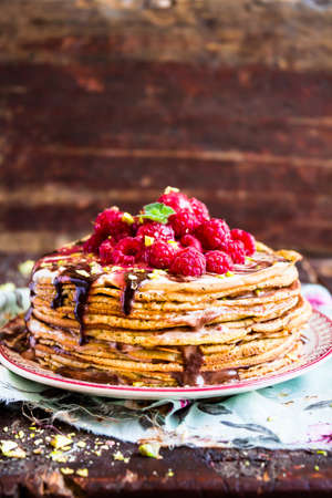 Stack of homemade thin pancakes or crepes or pancake cake with chocolate sauce, fresh raspberry, pistachios nuts decorated with fresh mint leaves on selective focus