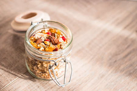 Healthy food granola with goji berry, almond nuts and peanuts in a jar on a wooden table, selective focus. Image with copy space.