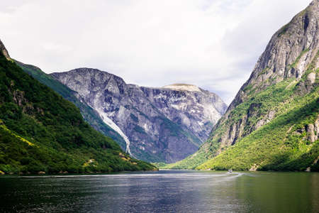 Beautiful nordic landscape with spectacular norwegian fjord - long, narrow inlet with steep sides or cliffs, created by a glacier. Image with copy space. Nature background. Mountains background.