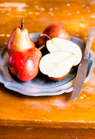 Fresh ripe red pears on a plate on a wooden table, selective focus. Raw organic food. Healthy food. Image with copy space.