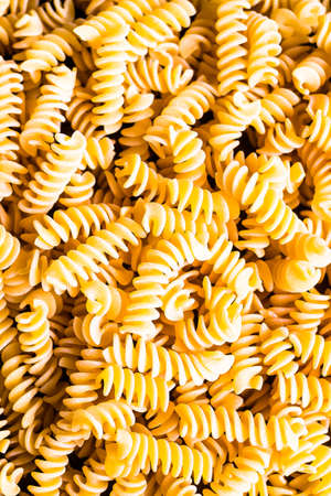 Uncooked whole wheat fusilli italian pasta background, selective focus. Pasta pattern. Food background.