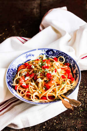 Traditional italian food. Bowl of homemade pasta spaghetti with fried shrimps or prawns, roasted red bell pepper, salted crumbled feta cheese, fresh dill on a wooden table, selective focus. Stock Photo