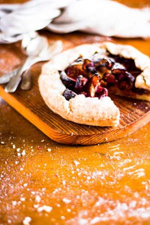 Homemade galette pie with ripe figs and raspberry dusted with icing sugar on a wooden table, selective focus. Piece of sweet fruit pie. Autumn collection. Stock Photo
