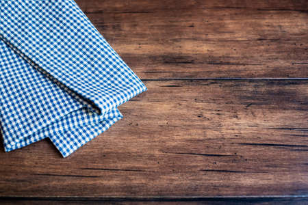 Stacked checkered blue napkins on an old wooden brown background, selective focus. Image with copy space. Kitchen table with linen towels.