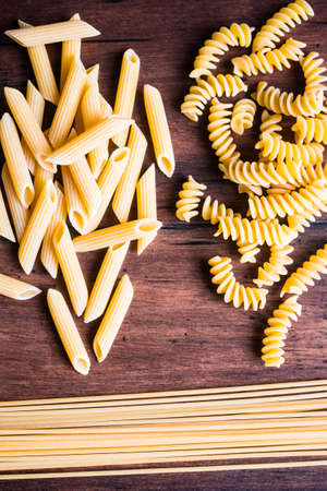 Variety of types and shapes of dry Italian pasta - fusilli, spaghetti and penne, top view. Uncooked whole wheat italian pasta. Image with copy space.