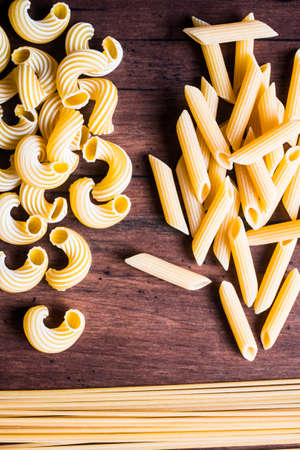 Variety of types and shapes of dry Italian pasta - cavatappi, spaghetti and penne, top view. Uncooked whole wheat italian pasta. Image with copy space.