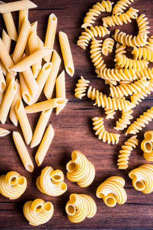Variety of types and shapes of dry Italian pasta - fusilli, cavatappi and penne, top view. Uncooked whole wheat italian pasta. Image with copy space.
