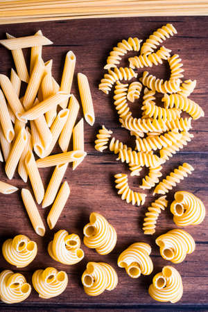 Variety of types and shapes of dry Italian pasta - fusilli, cavatappi, spaghetti and penne, top view. Uncooked whole wheat italian pasta. Image with copy space.