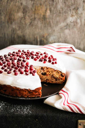 Cake with dried fruits and nuts decorated with sweet vanilla meringue and fresh cranberry dusted with icing sugar on a plate, selective focus. Easter cake. Image with copy space.