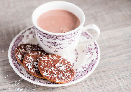 Cup of hot cocoa drink or hot chocolate with vanilla cookies coated in milk chocolate and sprinkled with freshly shredded coconut on a dessert plate on a wooden table, selective focus. Food for breakfast. Christmas food.