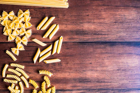 Italian pasta - spaghetti and penne, top view. Uncooked whole wheat italian pasta. Image with copy space.