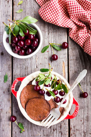 Chocolate pancakes with vanilla cream and ripe cherry in a plate on top of a wooden table. Breakfast food. Morning style. Healthy and organic food option. Stock Photo