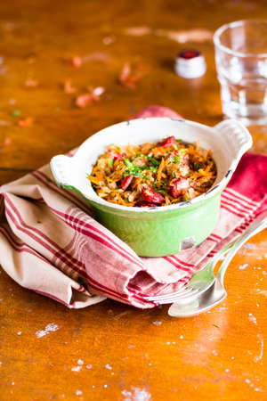Traditional polish food. Bigos, stewed cabbage with carrot, onion, green lentil and pork meat sausages in a pot on a wooden table, selective focus. German cuisine. Comfort food. Stock Photo