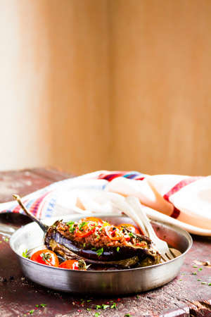 Traditional turkish dish of eggplant. Baked in the oven stuffed eggplant with pork and beef meat, red hot chili pepper, cherry tomatoes in a pan on a wooden table, selective focus. Comfort food. Stock Photo - 108961505