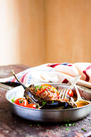 Traditional turkish dish of eggplant. Baked in the oven stuffed eggplant with pork and beef meat, red hot chili pepper, cherry tomatoes in a pan on a wooden table, selective focus. Comfort food.