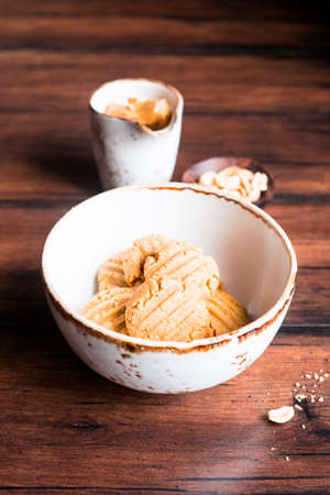 Heap of homemade peanut butter cookies in a bowl with a plate of peanuts and a cup of peanut butter on a wooden table, selective focus. Image with copy space. Traditional american treat. Stock Photo