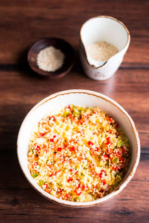 Couscous salad with red and green bell pepper, sesame seeds in a bowl on a wooden table, selective focus. Warm salad. Healthy and organic food concept. Stock Photo