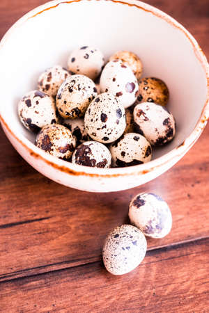 Quail eggs on a wooden vintage table, selective focus. Healthy and organic food option. Easter food. Easter symbol. Stock Photo