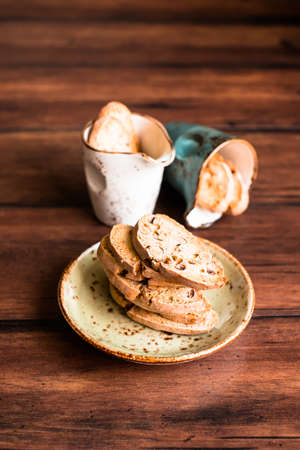 Italian dry cookies cantucci or biscotti with almond nuts stacked on a dessert plate on a wooden table, selective focus. Image with copy space. Easter food. Stock Photo