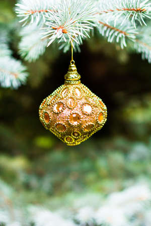 Golden tree decoration decoration hanging on a christmas tree, selective focus. Christmas postcard. Holiday concept.