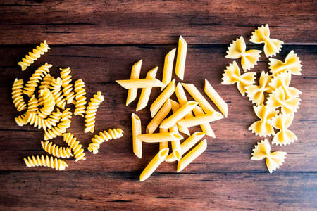 Variety of types and shapes of dry Italian pasta - fusilli, farfalle or bow tie pasta and penne, top view. Uncooked whole wheat italian pasta. Image with copy space.