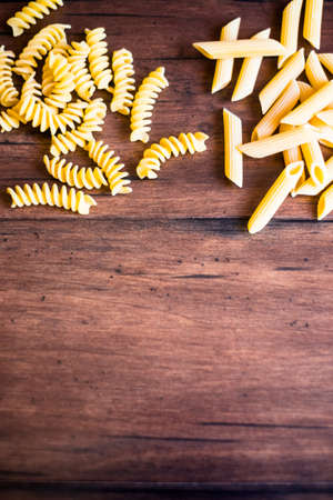 Variety of types and shapes of dry Italian pasta - fusilli and penne, top view. Uncooked whole wheat italian pasta. Image with copy space.