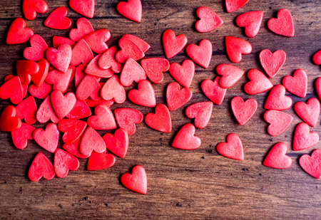 Red heart shaped candies on a wooden brown Stock Photo