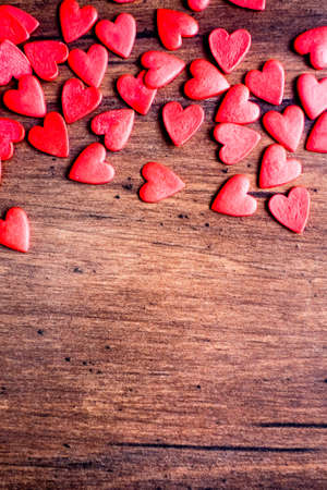 Valentines Day background, top view. Red heart shaped candies on a wooden brown background. The concept of Valentines Day.